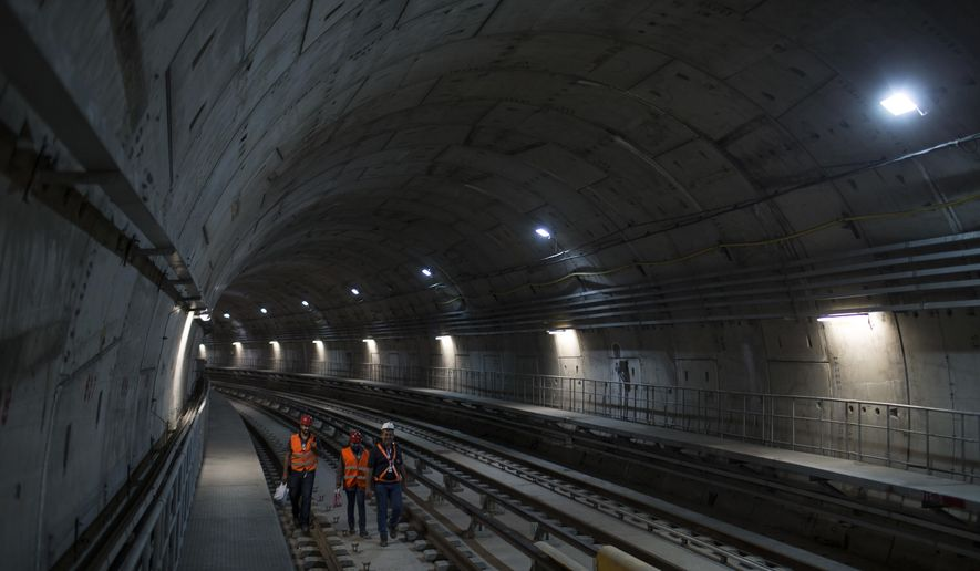 In this June 8, 2016 photo, men work in the new underground subway tunnel below Ipanema neighborhood in Rio de Janeiro, Brazil. With weeks before the summer Olympic games commence, a subway expansion that was supposed to transport hundreds of thousands of athletes and fans is not done. While officials insist it can still be finished in time, frequent delays, skyrocketing costs and a financing snag have created doubts. (AP Photo/Felipe Dana)