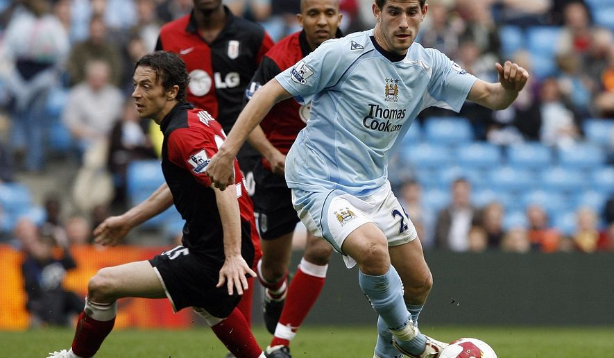FILE - In this Sunday April 12, 2009 file photo, former Manchester City's Ched Evans, right, evades Fulham's Simon Davies, left, during their English Premier League soccer match at the City of Manchester Stadium, Manchester, England. Ched Evans awaiting a retrial after his conviction for rape was overturned has signed a one-year contract with Chesterfield, a third-tier English club on Monday June 20, 2016. (AP Photo/Paul Thomas, File)