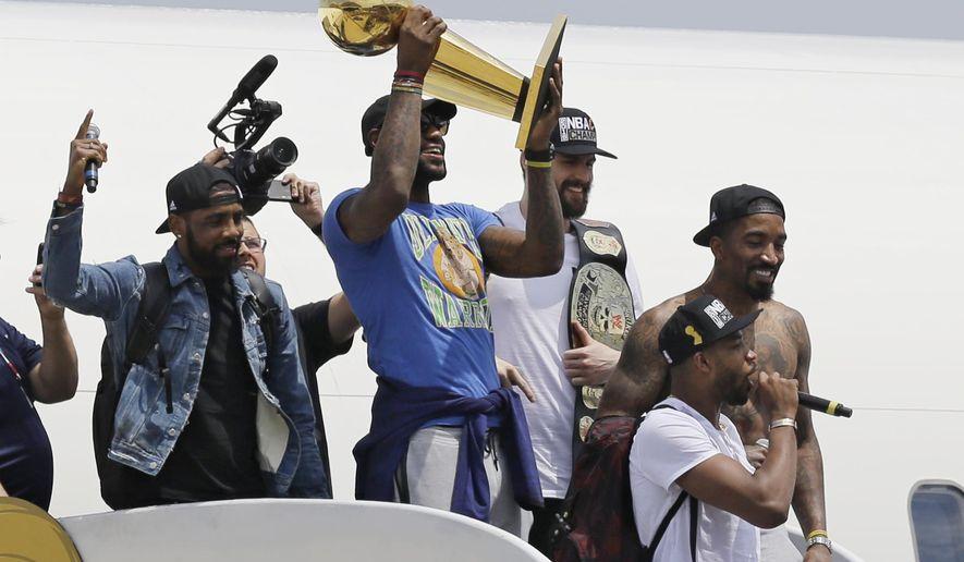 Cleveland Cavaliers' LeBron James holds up the NBA Championship trophy alongside teammates after arriving in Cleveland, Monday, June 20, 2016. (AP Photo/Tony Dejak)
