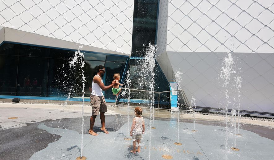 In this Sunday, June 19. 2016 photo, Aalin Askew, left, lifts his son Jaxon Askew as Saige Cummins watches at the fountain area in front of the Polk Penguin Conservation Center at the Detroit Zoo, in Royal Oak, Mich. The Detroit Free Press reports the fountain includes more than two-dozen water jets that blast upward and features an outline of Antarctica. During the winter months it will become an ice skating rink. (Regina H. Boone/Detroit Free Press via AP)  DETROIT NEWS OUT; TV OUT; MAGS OUT; NO SALES; MANDATORY CREDIT DETROIT FREE PRESS