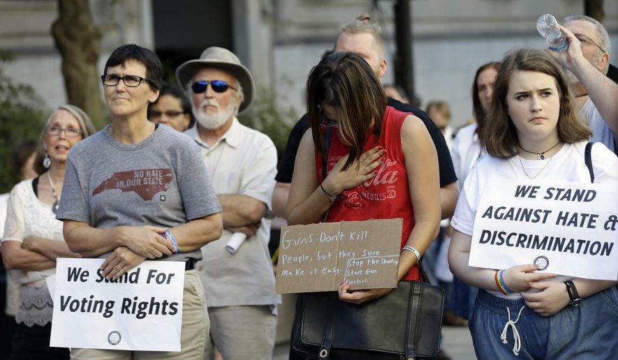 Participants attend a Moral Monday rally near the North Carolina Legislature in Raleigh, N.C., Monday, June 20, 2016. Victims of violence including the recent Orlando shooting and the Charleston shooting were honored during the rally. (AP Photo/Gerry Broome)