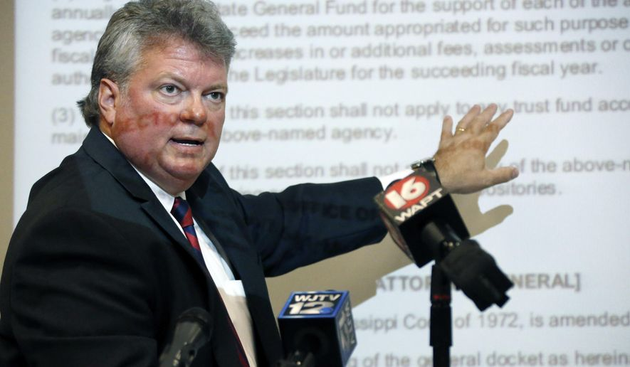 """Using a projected copy of Senate Bill 2362 as his background, Mississippi Attorney General Jim Hood explains his concerns about the """"Mississippi Budget Transparency and Simplification act of 2016"""" and its effect on various state programs trust funds, at a news conference Monday, June 20, 2016 in Jackson, Miss. (AP Photo/Rogelio V. Solis)"""