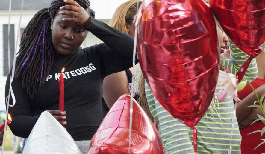 A woman takes a moment of silence as people gather for a vigil to remember the life of a 17-year-old in Muskegon, Mich., Sunday, June 19, 2016. Muskegon police said the teen was fatally shot and two other teenagers were wounded. (Joel Bissell/Muskegon Chronicle-MLive.com via AP) MANDATORY CREDIT