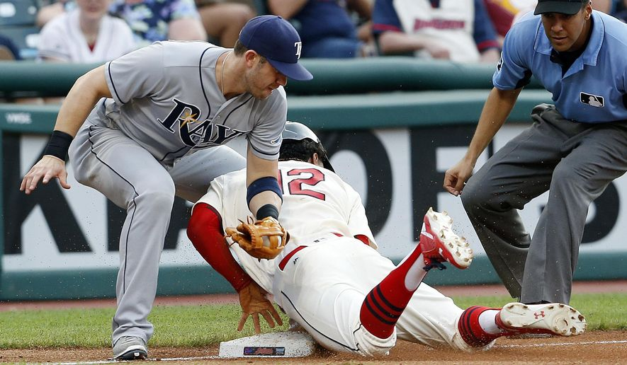Cleveland Indians' Francisco Lindor (12) steals third base as Tampa Bay Rays' Evan Longoria tries to tag him while third base umpire Gabe Morales waits to make the call during the fourth inning of a baseball game, Monday, June 20, 2016, in Cleveland. (AP Photo/Ron Schwane)