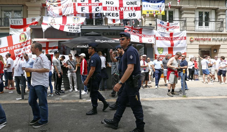 French police officers patrol past England supporters having a beer in Saint-Etienne, France, Monday, June 20, 2016 ahead of the Euro 2016 Group B soccer match between Slovakia and England at the Geoffroy Guichard stadium. (AP Photo/Darko Bandic)