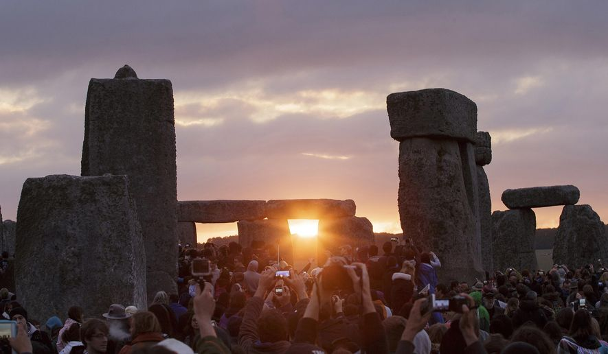 FILE - In this June 21, 2015, file photo, the sun rises as thousands of revelers gathered at the ancient stone circle Stonehenge to celebrate the Summer Solstice, the longest day of the year, near Salisbury, England. The solstice occurs Monday, June 21, 2016, at 6:34 p.m. on the U.S. East Coast. (AP Photo/Tim Ireland, File)