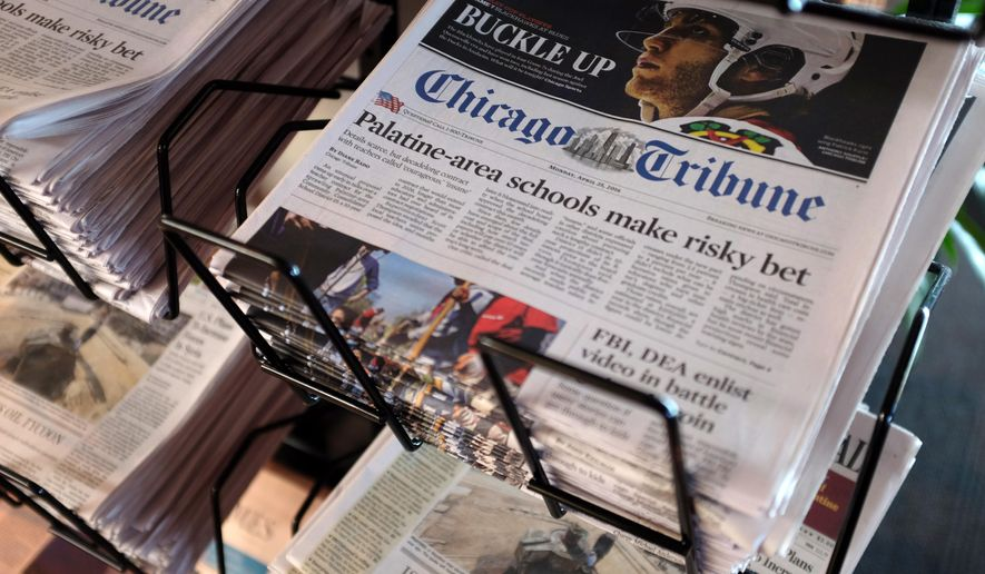 FILE - In this Monday, April 25, 2016, file photo, Chicago Tribune and other newspapers are displayed at Chicago's O'Hare International Airport. The Tribune newspaper company has officially changed its name to Tronc, which stands for Tribune online content, the company said. (AP Photo/Kiichiro Sato, File)