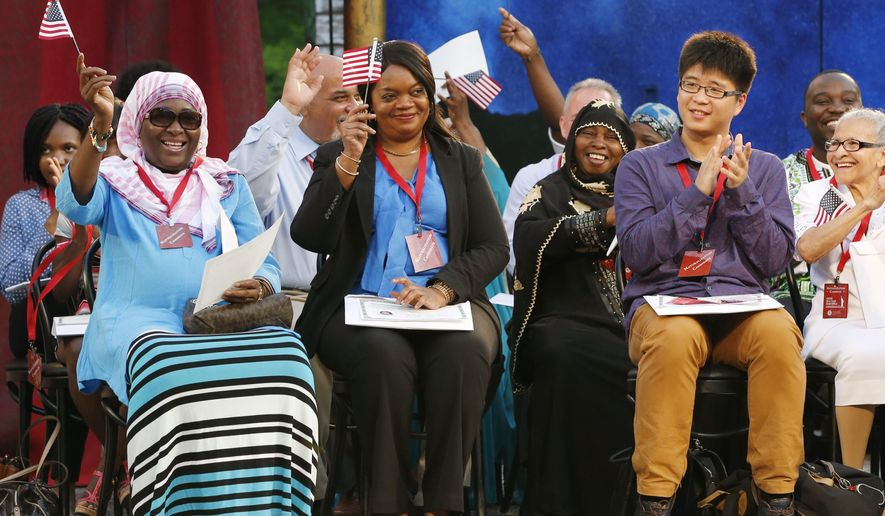 A group of 19 new U.S. citizens wave U.S. flags and celebrate on stage after they participated in a U.S. naturalization ceremony on World Refugee Day at the Delacorte Theater in Central Park, Monday, June 20, 2016, in New York. The International Rescue Committee, Department of Homeland Security and the Public theater helped commemorate the day by welcoming the immigrants from all over the world. (AP Photo/Kathy Willens)