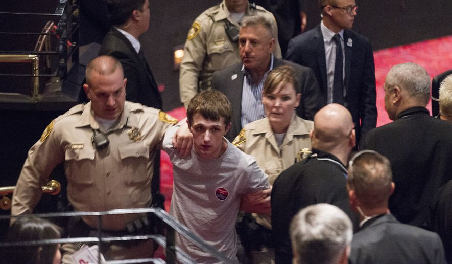 In this photo taken June 18, 2016, police remove Michael Steven Sandford as Republican presidential candidate Donald Trump speaks at the Treasure Island hotel and casino in Las Vegas. Sandford, from Britain, is accused of trying to take a police officer's gun and kill Donald Trump during the weekend rally in Las Vegas. (Erik Verduzco/Las Vegas Review-Journal via AP)