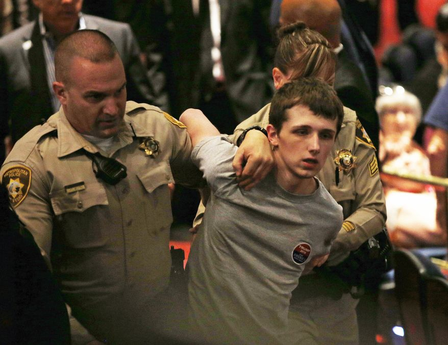 In this June 18, 2016, photo, police remove Michael Steven Sandford as Republican presidential candidate Donald Trump speaks at the Treasure Island hotel and casino in Las Vegas.(AP Photo/John Locher)