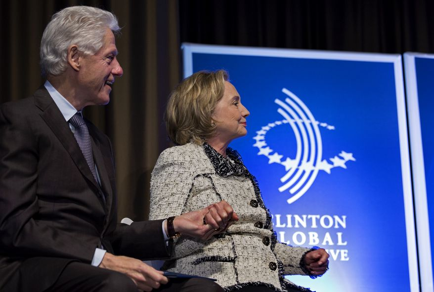 Former President Bill Clinton and former Secretary of State Hillary Clinton holds hands after she introduced Rio de Janiero Mayor Eduardo Paes at the Clinton Global Initiative Mid-Year Meeting on May 6, 2013 in New York. (Associated Press)