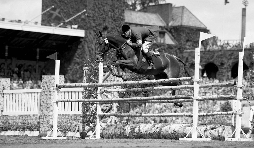 FILE - In this June 17, 1956, file photo, Frank Chapot, of the United States, clears a hurdle on his horse Bel Air during the first round of the Olympic Grand Prix in Stockholm, Sweden. The champion show jumper who competed in multiple Olympics before coaching the United States to Olympic gold has died. Chapot was 84. Wendy Chapot Nunn tells the Associated Press that her father died early Monday, June 20, 2016, at a nursing home in Bound Brook, N.J. (AP Photo/Leslie Priest, File)