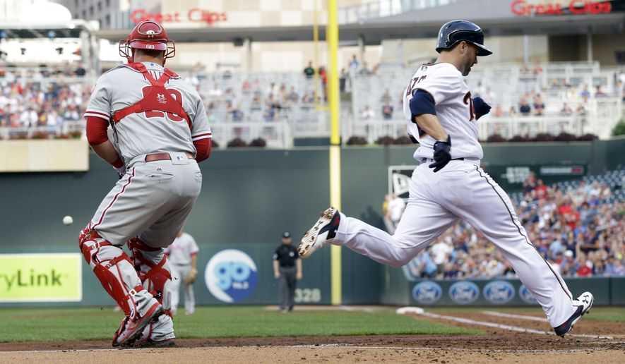 Minnesota Twins' Brian Dozier, right, scores on a two-run triple by Trevor Plouffe off Philadelphia Phillies pitcher Aaron Nola during the first inning of a baseball game Tuesday, June 21, 2016, in Minneapolis. Waiting for the throw is Phillies catcher Cameron Rupp. (AP Photo/Jim Mone)