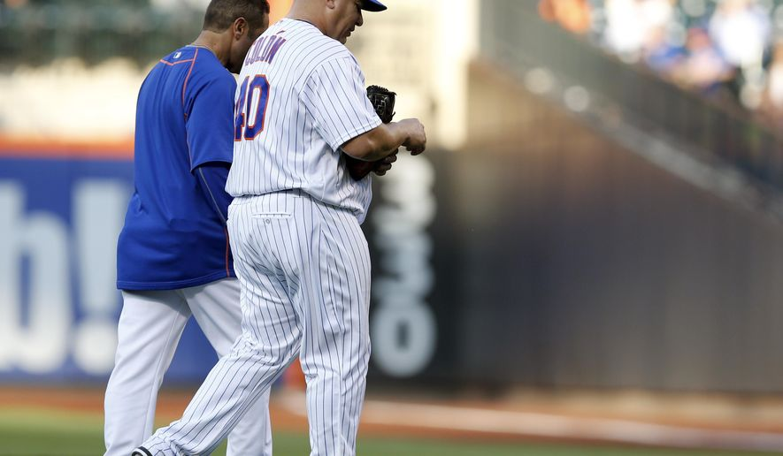 New York Mets starting pitcher Bartolo Colon, right, leaves the field with the Mets trainer after he was hit on the hand by Kansas City Royals Whit Merrifield's lead-off, ground ball during the first inning a baseball game against the Kansas City Royals, Tuesday, June 21, 2016, in New York. (AP Photo/Kathy Willens)