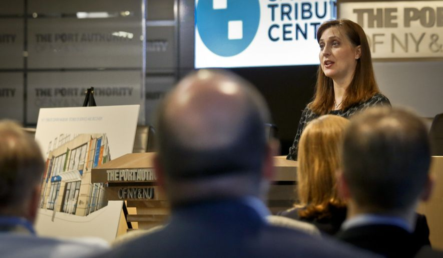 Jennifer Adams-Webb, right, CEO and co-founder for the September 11 Tribute Center, stands next to a rendering of the center's new museum, left, during a press conference, Tuesday, June 21, 2016, in New York. The Sept 11 Tribute Center, an exhibition center depicting events of 9/11, will move to a new expanded location near the World Trade Center. (AP Photo/Bebeto Matthews)