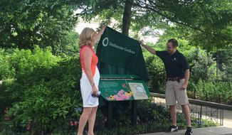Director Barbara Faust and Horticulturalist James Gagliardi reveal a newly designed sign for the Pollinator Garden . Formerly called the Butterfly Habitat Garden, the 400-foot-long path includes more than 250 species of colorful and fragrant plants, flowers and trees. (Photographs by Emily Kim/The Washington Times)