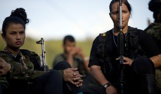 FILE - In this Jan. 4, 2016, file photo, Juliana, 20, left, and Mariana, 24, rebel soldiers for the 36th Front of the Revolutionary Armed Forces of Colombia, or FARC, listen to a commander speak on the peace negotiations between the rebels and the Colombian government, in a hidden camp in Antioquia state, in the northwest Andes of Colombia. Colombian President Juan Manuel Santos said Tuesday, June 21, that his government may reach an agreement on a bilateral ceasefire with leftist rebels as early as this week. (AP Photo/Rodrigo Abd,File)