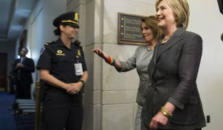 Democratic presidential candidate Hillary Clinton is escorted by House Minority Leader Rep. Nancy Pelosi of Calif. to a House Democratic caucus meeting on Capitol Hill in Washington, Wednesday, June 22, 2016. (AP Photo/Evan Vucci)