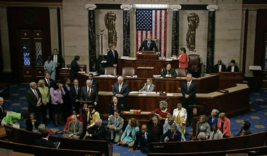 In this frame grab taken from AP video Georgia Rep. John Lewis, center, leads a sit-in of more than 200 Democrats in demanding a vote on measures to expand background checks and block gun purchases by some suspected terrorists in the aftermath of last week's massacre in Orlando, Florida, that killed 49 people in a gay nightclub.  Rebellious Democrats shut down the House's legislative work on Wednesday, June 22, 2016, staging a sit-in on the House floor and refusing to leave until they secured a vote on gun control measures before lawmakers' weeklong break.  (AP Photo)