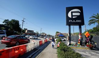 Traffic moves along Orange Avenue after authorities opened the streets around the Pulse nightclub, scene of the recent mass shooting, Wednesday, June 22, 2016, in Orlando, Fla. (AP Photo/John Raoux)