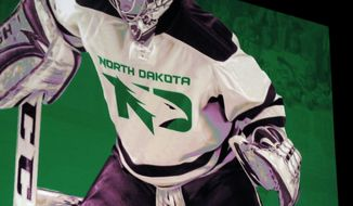 "A photo of a mock hockey jersey with the new University of North Dakota Fighting Hawks logo is seen at an unveiling ceremony at the Grand Forks, N.D., school on Wednesday, June 22, 2016. The school has been without a nickname for about four years after retiring its Fighting Sioux moniker the NCAA deemed to be ""hostile and abusive."" (AP Photo/Dave Kolpack)"