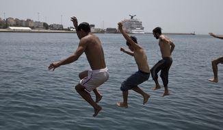 Afghan men jump into the sea from a dock of Athens's main Piraeus port where hundreds of refugees and migrants live,  Monday, June 20, 2016. The UN refugee agency marking World Refugee Day Monday June 20, said that on 2015, the world had 65.3 million people who had been forcibly displaced from their homes. (AP Photo/Petros Giannakouris)