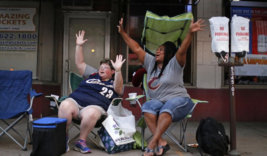 Misty Swegle, left, and Charlesetta Hawkins of Ashland, Ohio, have their spot for Wednesday's parade for the NBA champion Cleveland Cavaliers staked out on 9th Street by Tuesday evening, June 21, 2016, in downtown Cleveland. (AP Photo/Gene J. Puskar)