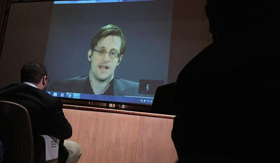 In this photo taken Feb. 17, 2016, former National Security Agency contractor Edward Snowden, center speaks via video conference to people in the Johns Hopkins University auditorium in Baltimore. (AP Photo/Juliet Linderman)