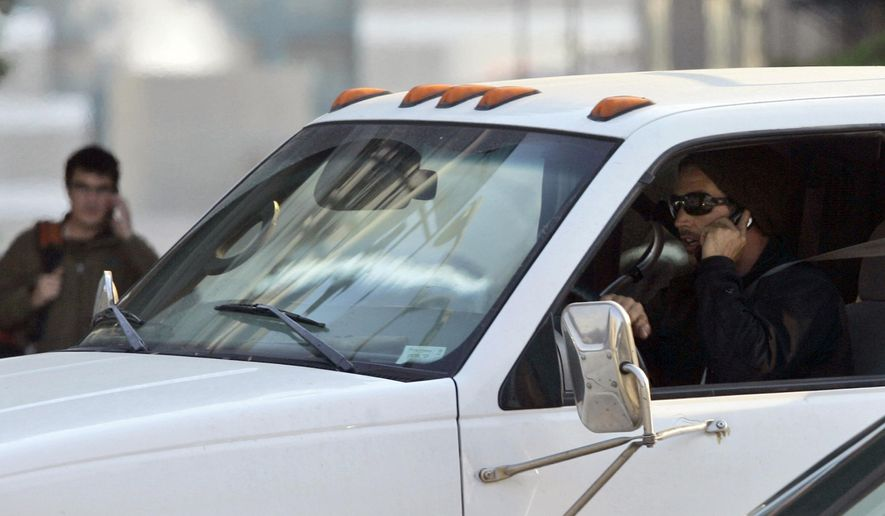 A driver talks on his mobile phone while driving in San Francisco in this June 24, 2008 file photo. New Jersey lawmakers are considering steep fines for distracted driving, starting at $400 for the first offense. (AP Photo/Jeff Chiu, File) **FILE**