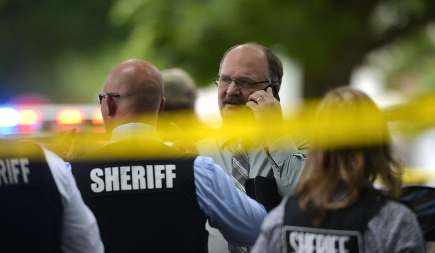 Police officials talk on the scene after a double stabbing on Wednesday, June 22, 2016, in Flint, Mich. (Rachel Woolf /The Flint Journal-MLive.com via AP) LOCAL TELEVISION OUT; LOCAL INTERNET OUT; MANDATORY CREDIT