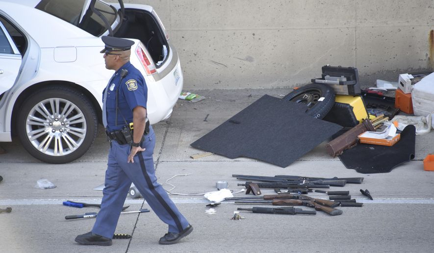 An arsenal of guns are on the pavement near a car involved in shooting on the Lodge freeway in Detroit, Tuesday, June 21, 2016. One man has been arrested following the shooting about 6 p.m. Tuesday. Police have recovered a number of handguns and long guns. (David Guralnick/The Detroit News via AP)
