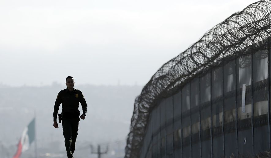 In this Wednesday, June 22, 2016, file photo, Border Patrol agent Eduardo Olmos walks near the secondary fence separating Tijuana, Mexico, background, and San Diego in San Diego. (AP Photo/Gregory Bull)