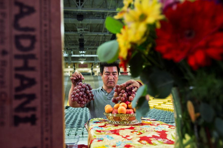 Amdo Nyima rearranges fruit as he helps the Tibetan Association of Colorado prepare for the Dalai Lama's visit in the Coors Event Center at Colorado University Boulder on Wednesday, June 22, 2016. (Autumn Parry/Daily Camera via AP) CREDIT