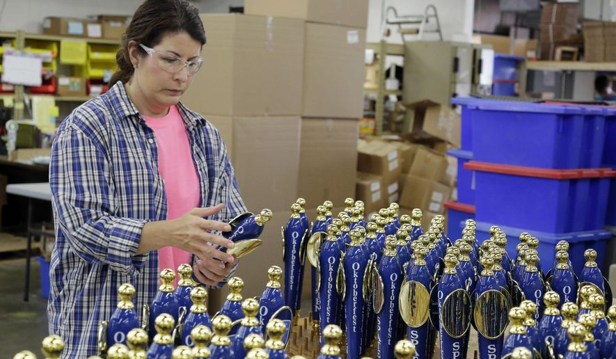 AJS Tap Handles' Tamara Theune does a final inspection on tap handles as she prepares them for shipment to a customer on June 15, 2016 in Random Lake, Wis.  Over the past decade, AJS and Associates has been rolling out increasingly elaborate tap handles as brewers seek new ways to stand out in an increasingly crowded marketplace. (Gary C. Klein/The Sheboygan Press via AP) NO SALES; MANDATORY CREDIT