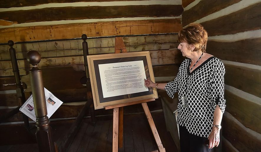 ADVANCE FOR USE SUNDAY, JUNE 26, 2016 AND THEREAFTER - In this June 9, 2016 photo, Cheryl Ranchino Trench talks about the history of the Hunter Log Cabin at The John A. Logan Harrison Bruce Historical Village in Carterville, Ill. The village consists of four historical buildings, dating from 1818 through the late 1800s. Located at John A. Logan College, it is open for public tours on on July 5 and July 19 2016 and continue into the fall. (Richard Sitler/The Southern via AP) MANDATORY CREDIT