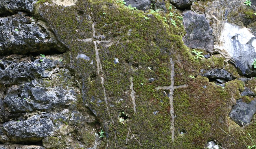 This undated photo, provided by the Hawaii Department of Land and Natural Resources, shows crosses etched by vandals on the crumbling remains of the 180-year-old summer palace of former King Kamehameha III in the forest of a Honolulu, Hawaii, neighborhood. The Department said Thursday, June 23, 2016, that unless the vandals are caught desecrating the sacred cultural site, there's little law enforcement officers can do.(Hawaii Department of Land and Natural Resources via AP) MANDATORY CREDIT
