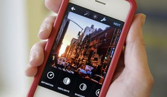 This June 9, 2014, file photo shows the Instagram app on an iPhone posed for a photo in New York. (AP Photo/Mark Lennihan, File)