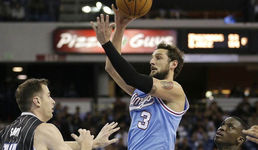 FILE - In this March 11, 2016, file photo, Sacramento Kings guard Marco Belinelli, center, of Italy, goes to the basket between Orlando Magic's Jason Smith, left, and Victor Oladipo during the second half of an NBA basketball game in Sacramento, Calif. A person familiar with the situation says the Charlotte Hornets have acquired Belinelli from the Kings in exchange for the 22nd pick in the NBA draft. The person spoke to The Associated Press on Thursday, June 23, 2016, on condition of anonymity because the trade won't become official until after the NBA's new salary cap season begins on July 7. (AP Photo/Rich Pedroncelli, File)