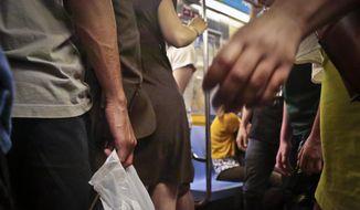 Subway riders board a train during rush hour, Wednesday, June 22, 2016, in New York. (AP Photo/Bebeto Matthews) ** FILE **