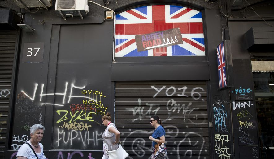 Women walk past a shuttered shop with a British flag in Athens, Friday, June. 24, 2016. Greece's prime minister says the British referendum dealt a severe blow to European unification, and should force a shift toward more democratic practices within the European Union.(AP Photo/Petros Giannakouris)