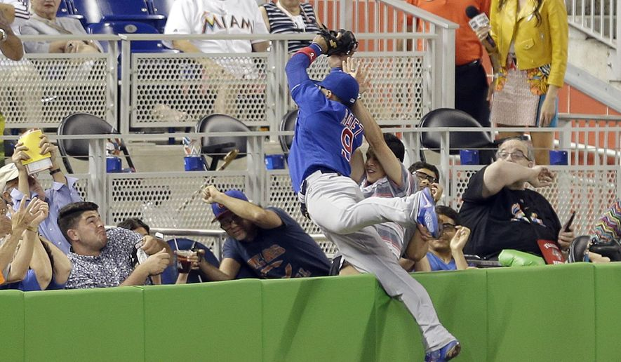 Chicago Cubs third baseman Javier Baez (9) catches a foul fly ball by Miami Marlins' J.T. Realmuto in the fourth inning of a baseball game, Friday, June 24, 2016, in Miami. (AP Photo/Alan Diaz)