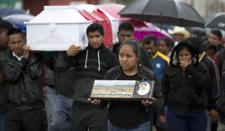 A young woman walks with a photo of Jesus Cadena, who died last Sunday during the clearing of the highway by police, as others carry his coffin in Nochixtlan, in Oaxaca state, Mexico, Tuesday, June 21, 2016. Violence erupted during the weekend in which at least 8 people died in confrontations between the police and striking teachers. The teachers are protesting against plans to overhaul the country's education system which include federally mandated teacher evaluations. (AP Photo/Eduardo Verdugo)