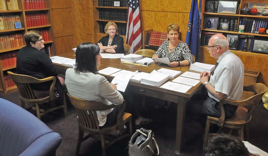 North Dakota Secretary of State Al Jaeger, right, convenes a meeting of the state canvassing board on Friday, June 24, 2016 at the state capitol in Bismarck.  The board met to certify election results from the 2016 June primary election.  Clockwise from Jaeger are board members Roz Leighton, executive director North Dakota Republican Party, Alison Tate, of the North Dakota Democratic Party, Penny Miller of the state supreme court and Kelly Schmidt, state treasurer.  (Tom Stromme/The Bismarck Tribune via AP) MANDATORY CREDIT