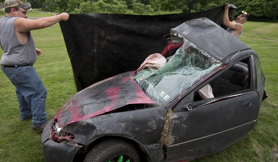 ADVANCE FOR USE SATURDAY, JUNE 25 - In this photo taken June 15, 2016, friends cover the mangled 1995 Honda Civic that Michael Posten, 27, of Wiconisco, Pa., died in May 28, 2016. His mother Sandra hopes to find some meaning in his death, possibly using the car to get kids to slow down. (Mark Pynes/PennLive.com via AP)