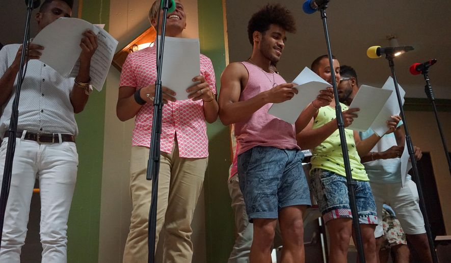 In this June 20, 2016 photo, Members of gay Cuban choir Mano a Mano rehearse with the gay Men's Chorus of Los Angeles. Both choirs have charted history in their respective LGBT communities. Mano a Mano is embarking on its first U.S. tour with a kick-off performance in Los Angeles Saturday. The tour comes as Washington and Havana renew diplomatic relations after decades of hostility. (AP Photo/Christine Armario)