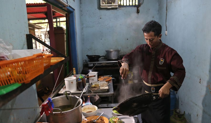 "In this Monday, May 16, 2016 photo, Mahmudi Haryono, 40, who is also known by his militant alias ""Yusuf Adirama"" cooks in the kitchen of his restaurant in Solo, Central Java, Indonesia. Haryono who also runs a car-hire business and a laundry service is one of the poster boys for the transformation of a jihadist into a productive member of society, a success owed to the work of a private group with limited funds that reaches only a minority of people. (AP Photo/Achmad Ibrahim)"