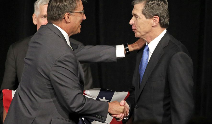 North Carolina Gov. Pat McCrory, left, shakes hands with North Carolina Attorney General Roy Cooper, right, after a candidate forum in Charlotte, N.C., Friday, June 24, 2016. The two men will face each other in November for governor in what could be the most expensive and watched gubernatorial election this year. (AP Photo/Chuck Burton)
