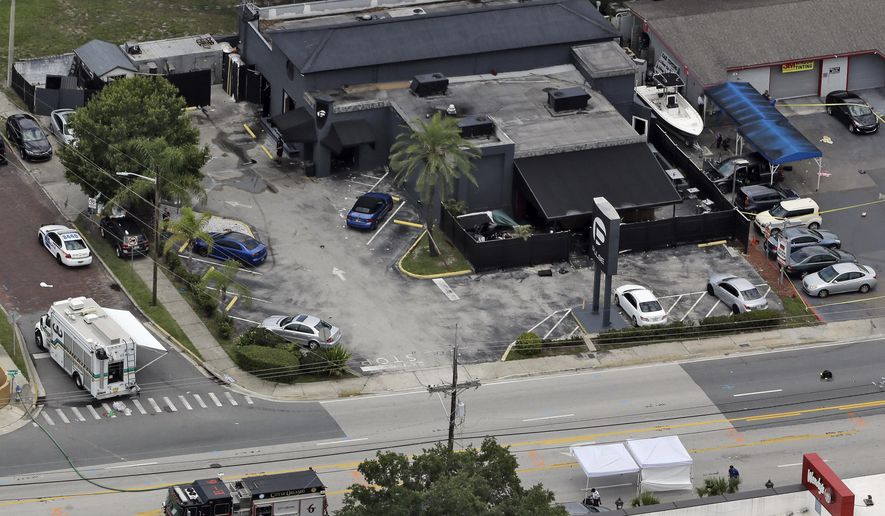 FILE - In this June 12, 2016 file photo, law enforcement officials work at the Pulse nightclub following a fatal shooting, in Orlando, Fla. Two government officials familiar with the Orlando shooting say FBI investigators have so far not turned up persuasive evidence that the gunman was pursuing gay relationships.  (AP Photo/Chris O'Meara, File)