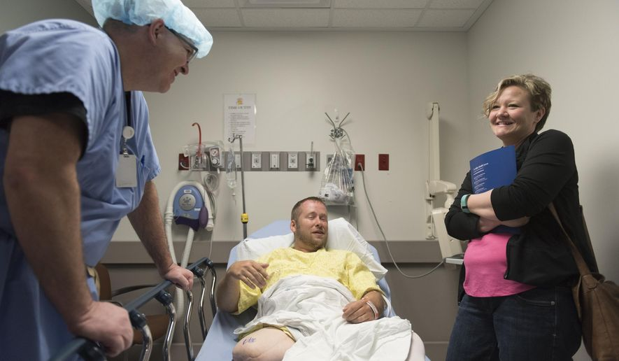 In this Friday, June 3, 2016 photo, Dr. Ronald Hillock, left, patient Anthony Reff, center, and his wife, Tina, prepare for Anthony's osseointegration surgery at Centennial Hills Hospital in Las Vegas. The Reffs came in from Breckenridge, Minn., for the surgery. (Jason Ogulnik/Las Vegas Review-Journal via AP) MANDATORY CREDIT