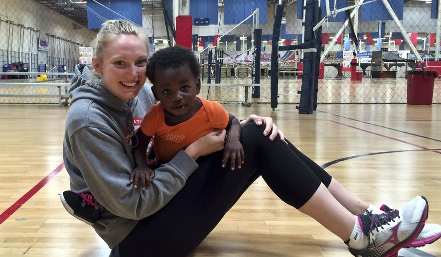 U.S. women's volleyball player Nicole Fawcett plays with Easton Easy, son of teammate Megan Easy, .Monday, May 23, 2016 in Anaheim, Calif. She is balancing motherhood and volleyball with support from coach Karch Kiraly. (AP Photo/Janie McCauley)